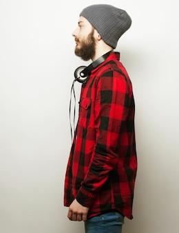 Concetto emotivo e di persone: giovane uomo barbuto che indossa un cappello con le cuffie
