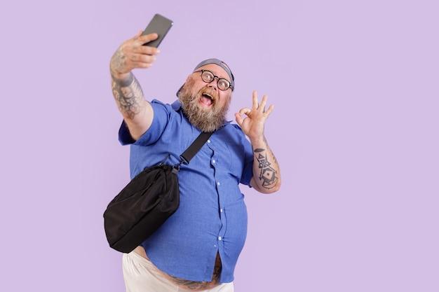 L'uomo hipster grassoccio emotivo con borsa a tracolla mostra il gesto ok prendendo selfie con il moderno telefono cellulare su sfondo viola in studio