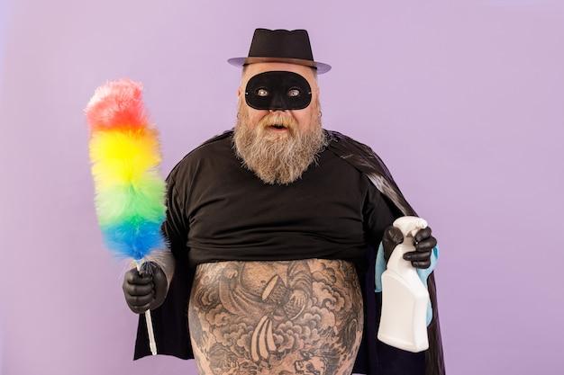 L'uomo grassoccio emotivo in tuta da eroe tiene pennello e flacone spray su sfondo viola