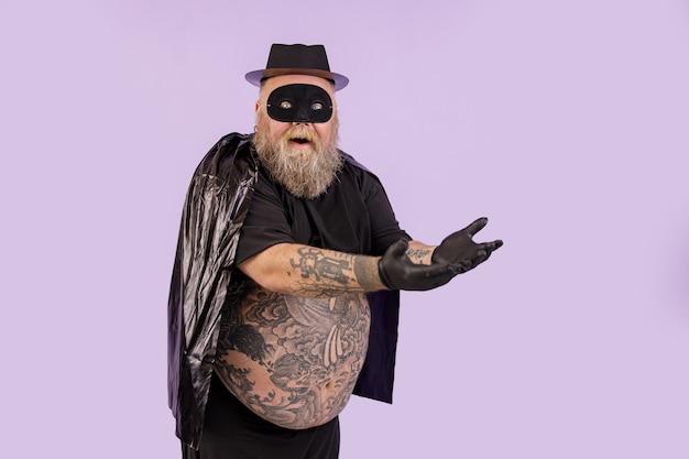 L'uomo emotivo plus size in abito da eroe nero mostra qualcosa su sfondo viola