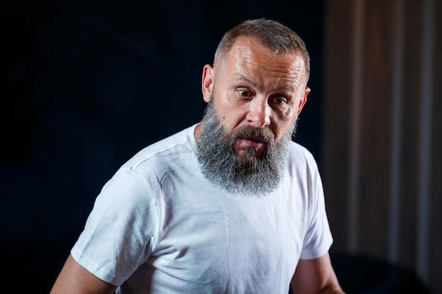 Ritratto emotivo di un uomo adulto dai capelli grigi con la barba in una maglietta bianca