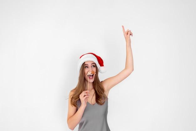 La ragazza emotiva di santa indossa i baffi finti alza la mano con la pubblicità del nuovo anno del dito indice