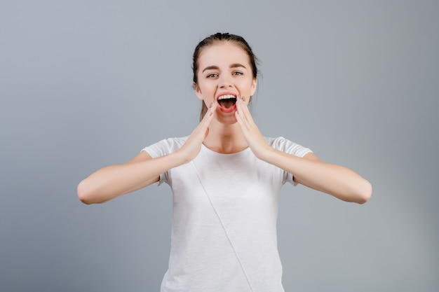 Bella donna castana di grido emozionale che copre la sua bocca di mani isolate sopra grey