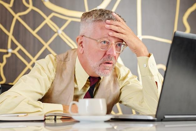 Imprenditore senior emotivo in vetri che leggono notizie scioccanti sullo schermo del laptop