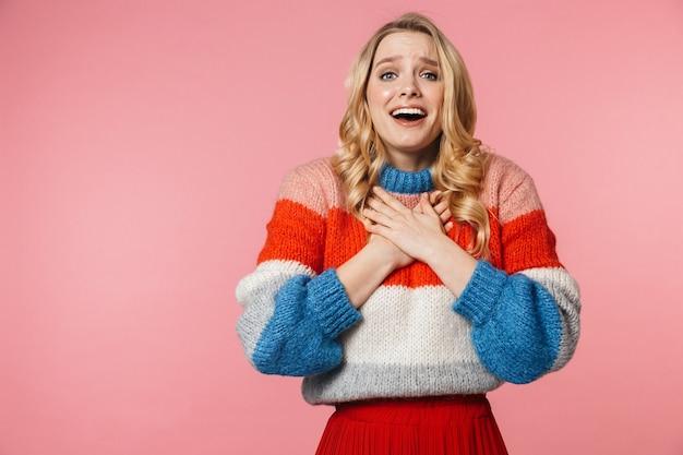 Giovane donna abbastanza bella scioccata emotiva in posa isolata sul muro rosa