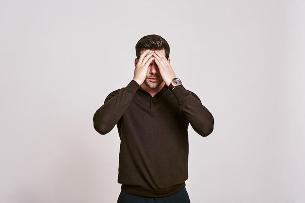 Stress emotivo uomo dai capelli scuri che si tocca la testa con la mano sentendo un forte mal di testa in piedi