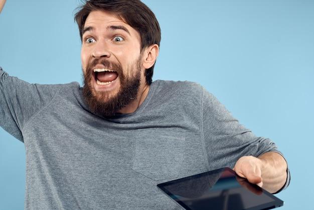 Uomo sorpreso emotivo con tablet in primo piano tecnologia mani