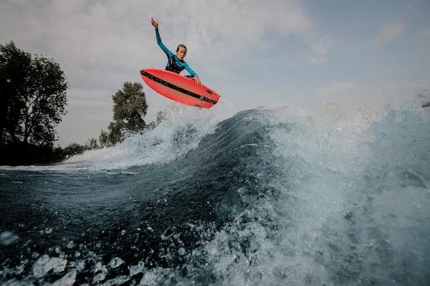 Ragazzo emozionale dell'adolescente che salta sul wakeboard arancio