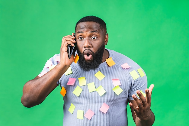 Uomo nero afroamericano stanco emotivo ha sottolineato a causa di molto lavoro e scadenza essendo deluso isolato su sfondo verde. uomo d'affari. utilizzo del telefono cellulare.