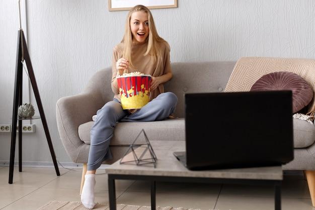 Donna emotiva sul divano con popcorn guardando la tv