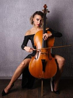 Donna emotiva in un abito da sera che suona il violoncello
