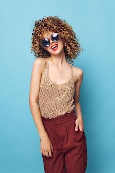Donna emotiva divertimento labbra rosse occhiali scuri vestiti alla moda stile di vita sfondo blu vista ritagliata