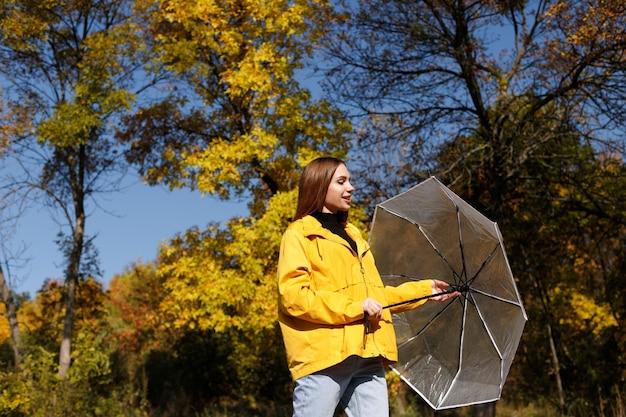 La donna emotiva sorride e distoglie lo sguardo con un ombrello su uno sfondo luminoso di foglie autunnali