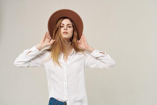 Emotiva donna che indossa cappello camicia bianca studio di moda vista ritagliata. foto di alta qualità