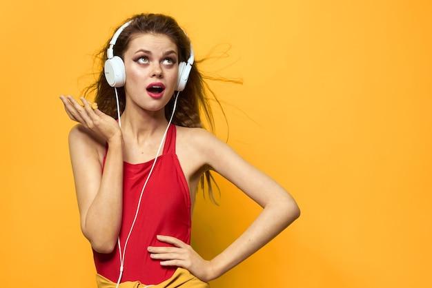 La donna emotiva in cuffie bianche ascolta il fondo giallo di stile di vita di divertimento di musica. foto di alta qualità