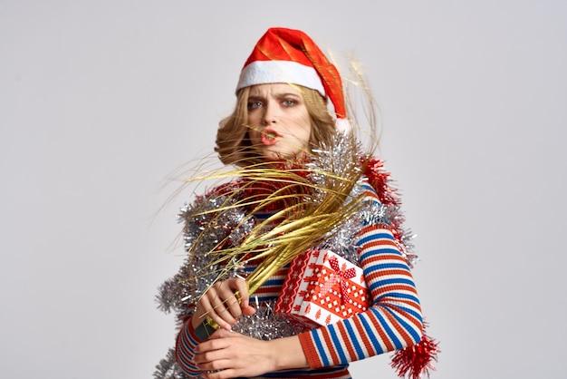 Donna emotiva con rami di un albero festivo e berretto rosso tinsel sulla sua testa a strisce sudate