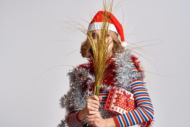 Donna emotiva con rami di un albero festivo e berretto rosso tinsel sulla sua testa a strisce