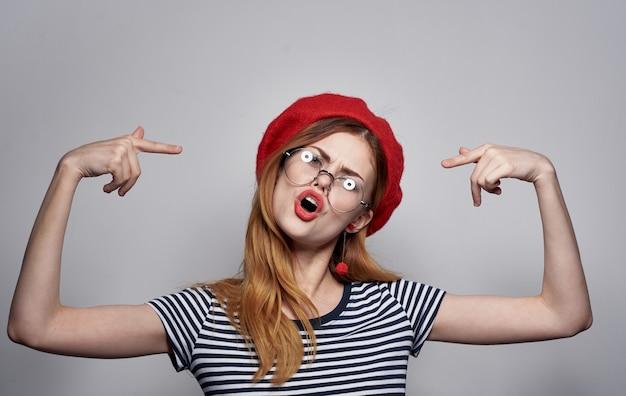 Una donna emotiva con gli occhiali e una maglietta a righe fa gesti con le mani.
