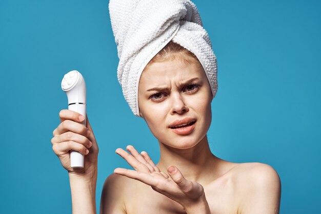 Donna emotiva con l'asciugamano sulla cura della pelle del massaggiatore facciale della testa