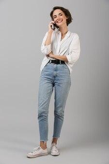 Emotivo giovane donna d'affari in posa isolato sopra il muro grigio parlando dal telefono cellulare