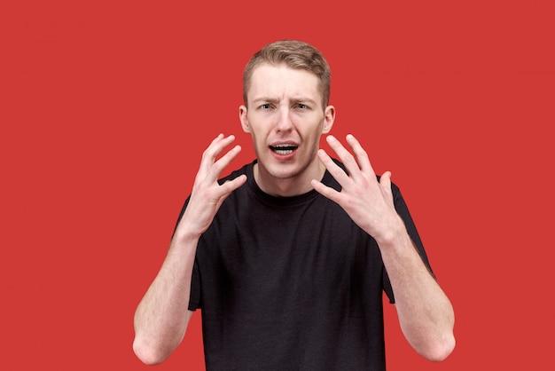 Giovane uomo caucasico emozionale in una maglietta nera che gesticola attivamente le mani con un'espressione indignata di dissenso. il concetto di irritabilità, rabbia, indignazione,