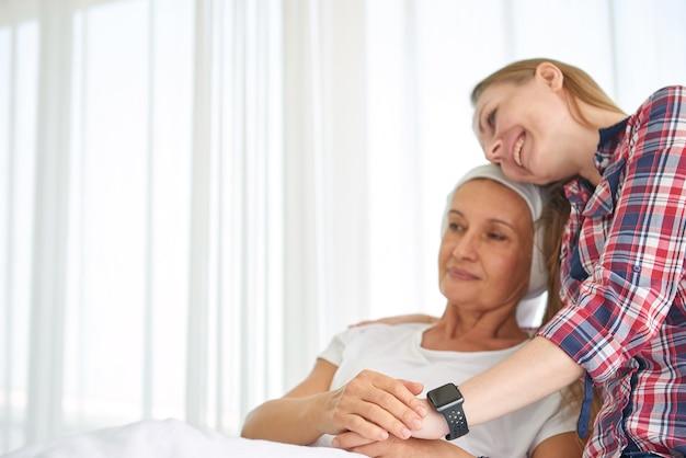 Emotivo della giovane figlia bianca caucasica con speranza e sorriso in visita e incoraggiare a sostenere sua madre che indossa la sciarpa e lotta con il cancro al seno nella stanza d'ospedale pulita e chiara