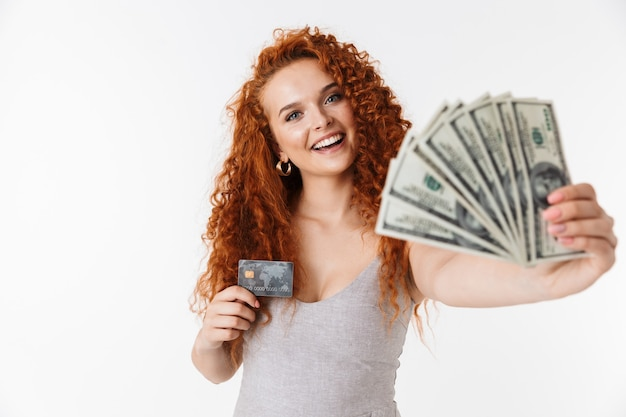 Giovane donna riccia rossa emotiva che tiene soldi e carta di credito.