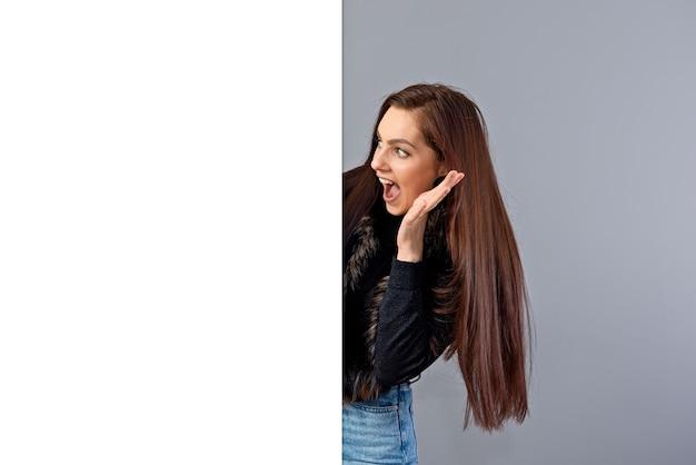 Emotiva giovane donna adolescente che mostra cartello bianco con copia spazio, isolato su grigio