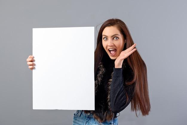 Giovane donna emotiva dell'adolescente che mostra insegna in bianco con lo spazio della copia, isolata su gray