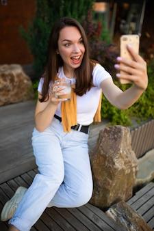 Emotiva giovane donna fa selfie sullo sfondo di un bellissimo parco verde.