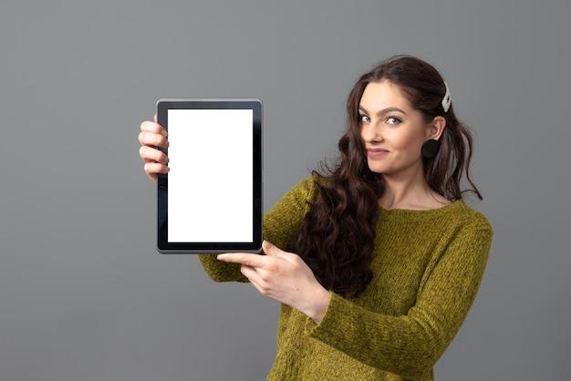Giovane donna emotiva che mostra computer tablet con touch screen vuoto con spazio di copia, isolato su superficie grigia