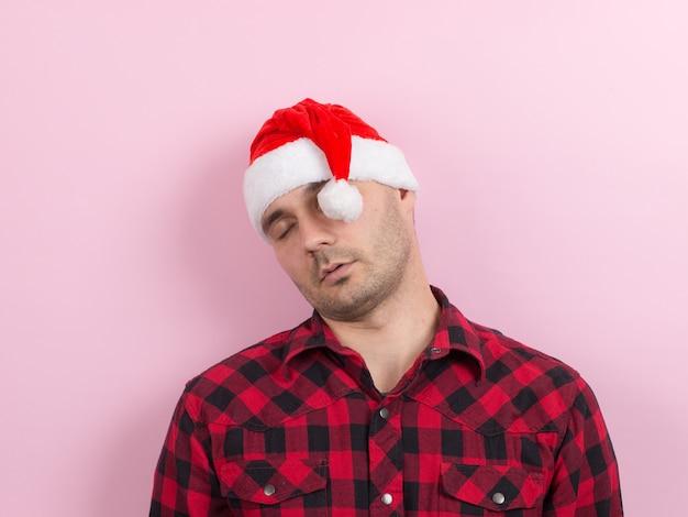 Emozioni sul viso, stanco, postumi di una vacanza, consapevolezza. un uomo in un coniglio plaid e un cappello rosso di natale