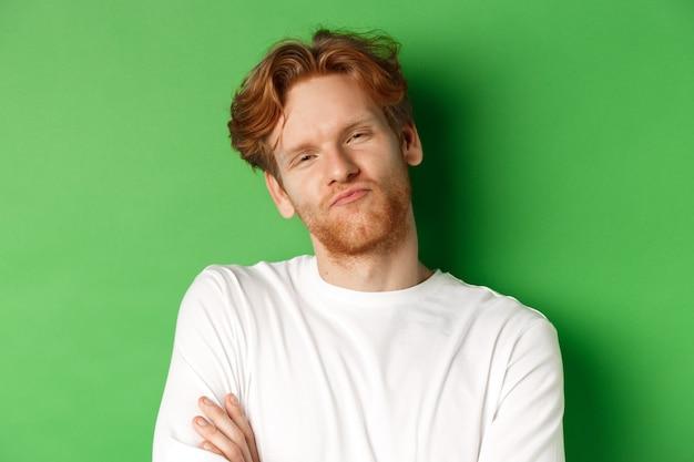Le emozioni e il concetto di moda in primo piano di un giovane scettico con i capelli rossi e le labbra increspate della barba sembrano...