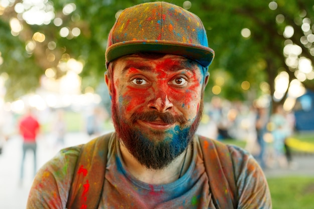 Emozioni, persone, bellezza, moda e concetto di lifestyle - il giovane imbrattato di colori interpreta holi
