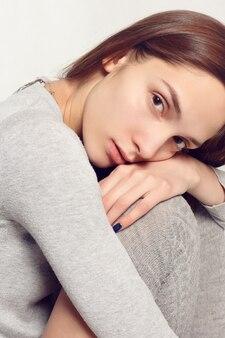 Emozioni, persone, bellezza e concetto di stile di vita - ritratto di giovane ragazza alla moda in calze grigie, un classico maglione caldo su sfondo grigio. stile vogue. colpo dello studio. test del modello
