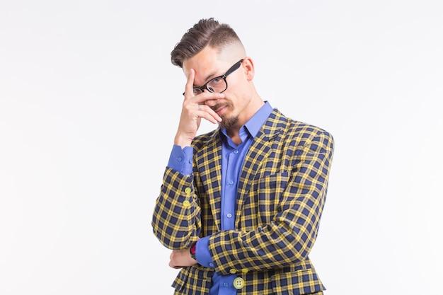 Emozioni e concetto di persone - bel giovane in giacca con barba e baffi in bicchieri pensando a qualcosa sopra il muro bianco.