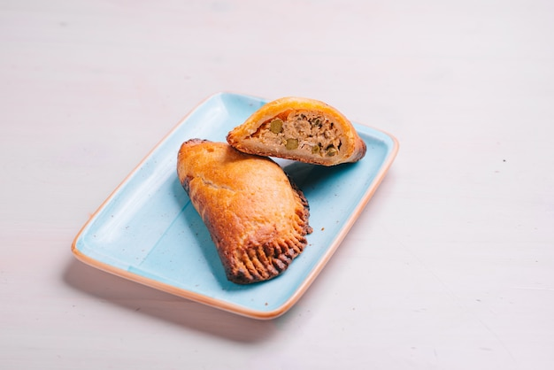 Empanada, torta di carne su un piatto e superficie bianca