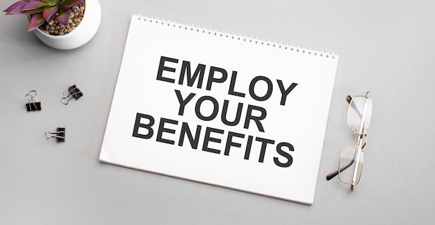Utilizza i tuoi benefici è scritto su un quaderno bianco accanto a una matita