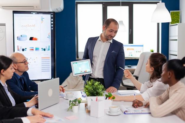 Dipendente che fa domande esecutive durante il briefing di presentazione della presentazione della sala conferenze