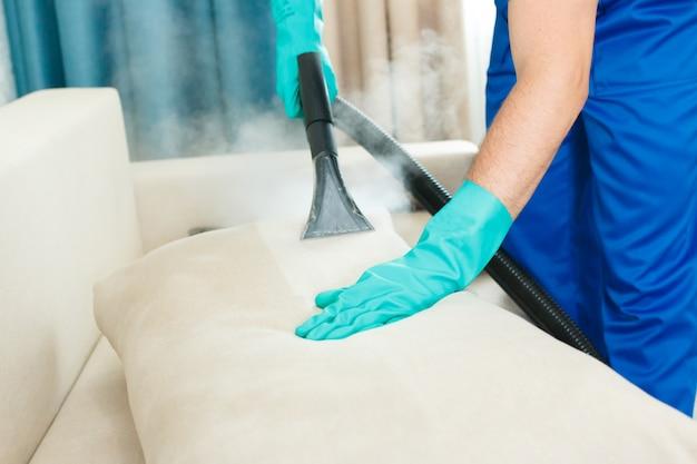 Un dipendente di un'impresa di pulizie fornisce un servizio di pulizia chimica e a vapore per il divano. pulitore a vapore