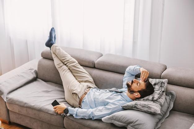 Impiegato vestito elegante sdraiato sul divano in soggiorno e prendendo una pausa dal lavoro.