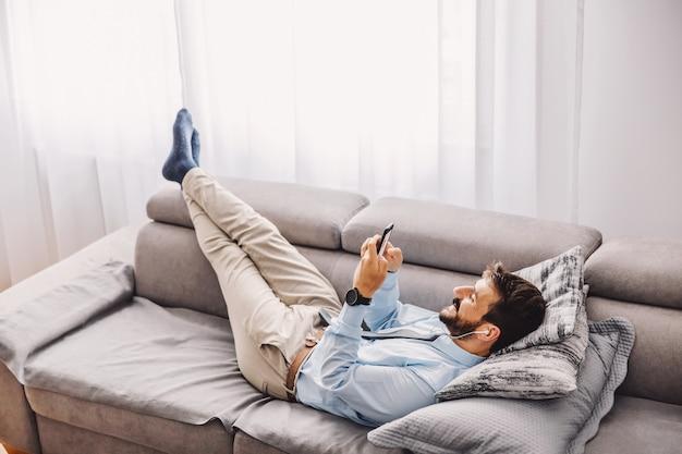 Dipendente sdraiato sul divano e utilizzando il telefono cellulare durante la quarantena. epidemia di covid concetto.