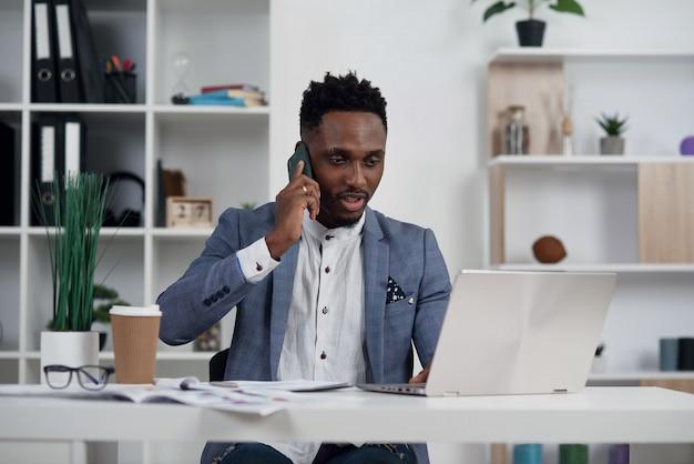 L'impiegato che fa la chiamata di affari si è concentrato sul computer portatile nel suo luogo di lavoro. cliente consultantesi dell'uomo d'affari nero, discutente rapporto finanziario. negoziazione del contratto e concetto di discussione