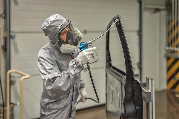 Un dipendente dell'officina di verniciatura dello stabilimento automobilistico conduce una formazione sull'applicazione del sigillante