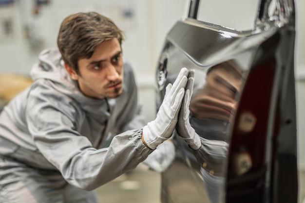 Un dipendente dell'officina di verniciatura dello stabilimento automobilistico conduce una formazione sulla preparazione dei paraurti per la verniciatura