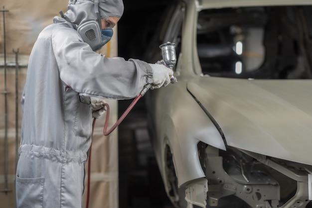 Dipendente che vernicia la carrozzeria dell'auto