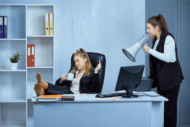Un dipendente mostra il dito medio al suo capo, che gli urla attraverso un megafono