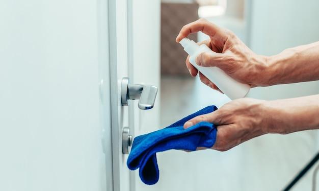 Dipendente che spruzza uno spray antibatterico sulla maniglia della porta