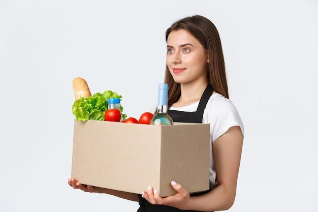 Dipendenti, consegna e ordini online, concetto di negozi di alimentari. profilo di bella commessa carina, cassiera in grembiule nero con scatola con generi alimentari, cibo e bevande, gestione dell'ordine al cliente.