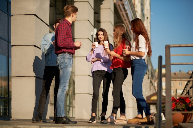 Dipendenti che si godono una tazza di caffè durante la pausa. giovani studenti che discutono del loro progetto all'aperto